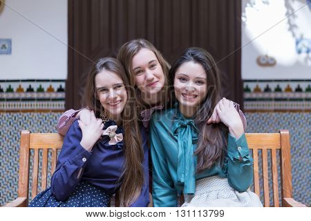 Three girlfriends smiling while hugging on bench