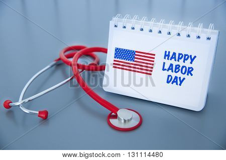 Notebook with printed text HAPPY LABOR DAY and stethoscope on grey background