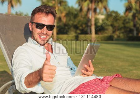 happy youn man making ok thumbs up sign while sitting on a long chair and reading on his tablet pad computer