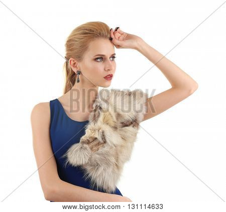 Young beautiful blonde girl wearing perfect makeup and dress in a fur over white studio background