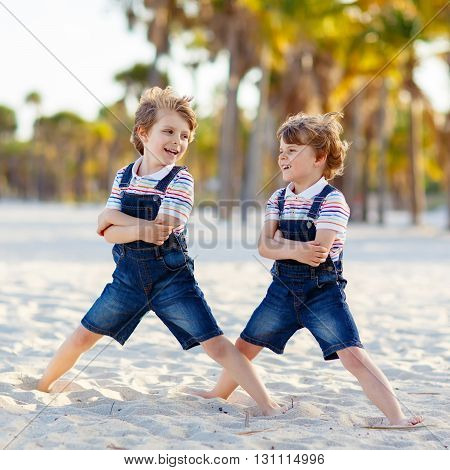 Two little kids boys having fun on tropical beach, happy best friends playing, friendship concept. Siblings brothers in family look with palms on background