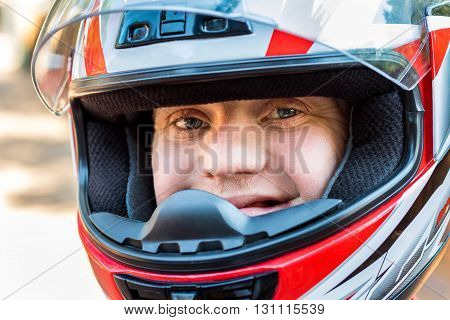 Close up face shot of young sportsman with down syndrome wearing helmet.