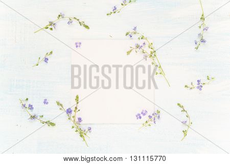 Scrapbooking page of wedding or family photo album frame with fresh blue flowers on light wooden background; top view flat lay overhead view