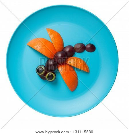 Dragonfly made of orange and grape on plate