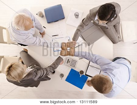 Businesspeople holding hands united over meeting table, while teamworking, high angle view.?