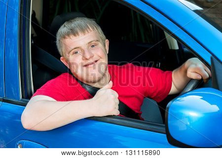 Close up portrait of young handicapped car driver sitting behind steering wheel doing thumbs up symbol.