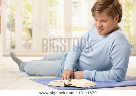 Young man reading book lying on living room floor, smiling.?