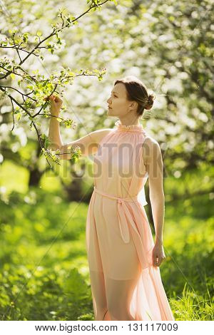 Young woman standing near to blooming apple tree