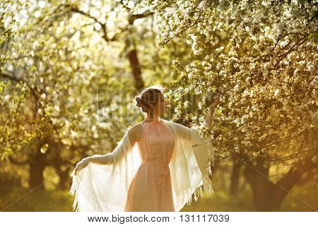 Woman in a pink dress near blooming apple tree