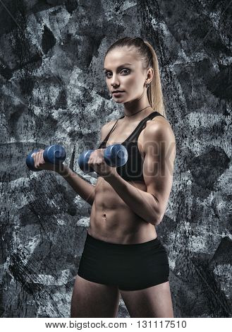 Young sports sexy fitness woman with dumbbells posing on wall background.
