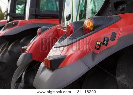 Row of red heavy farming tractors vehicle