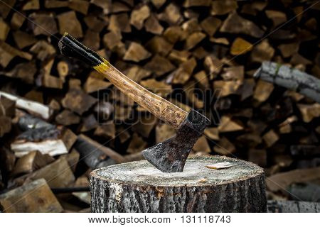 the old axe stuck in a stump on a background of chopped firewood