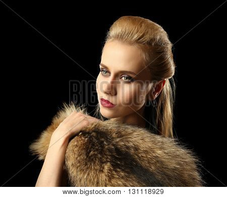Beautiful young woman with luxury fur on dark background