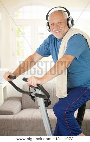 Sporty senior listening to music via headphones while exercising on stationary bike, at home, smiling at camera.?