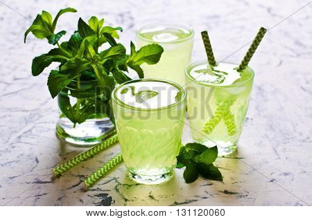 Cold drink with mint in a glass on a concrete background. Selective focus.