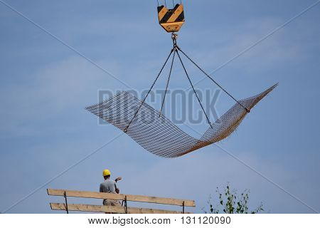 Craftsman on construction site - steel mesh is transported by crane