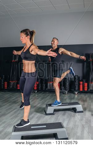 Athletic couple doing exercises over steps in aerobic class on a fitness center. Sport and health concept.