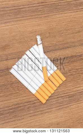 Tobacco burning cigarette detrimental on wood background select focus front