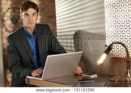 Handsome businessman working with laptop computer, looking at camera.