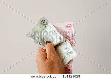 A Hand holding 2 notes on white BG