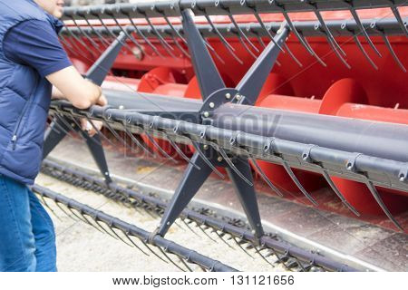 Worker is resting on red combine after harvest