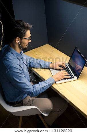 Handsome businessman working late at night in an office