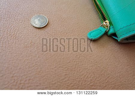 A green purse and a coin on ground