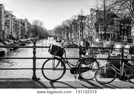 Monochrome backlit image overlooking the Prinsengracht from bridge 64 (Reesluis). It is early in the morning on a sunny day in the winter season.