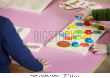 Children playing with homemade do-it-yourself educational toys arranging and sorting colors and sizes. Learning through experience concept intelligence development educational approach concept.