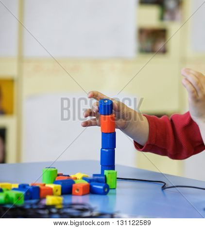 Child playing with homemade do-it-yourself educational toys stacking and arranging colorful pieces. Learning through experience concept gross and fine motor skills educational approach concept.