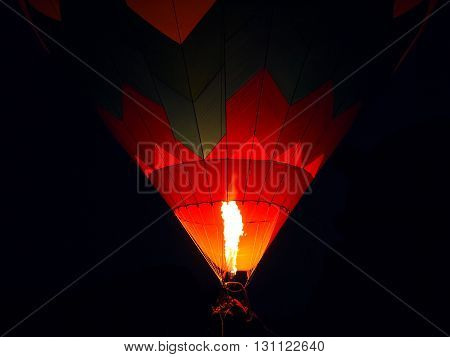 The crew basket flame and ropes of a hot air balloon against a dark blue black night sky.