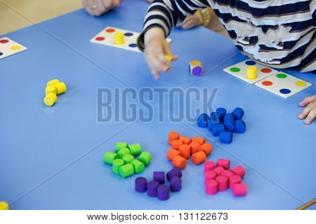 Children playing with homemade do-it-yourself educational toys arranging and sorting colors. Learning through experience concept intelligence development educational approach concept.