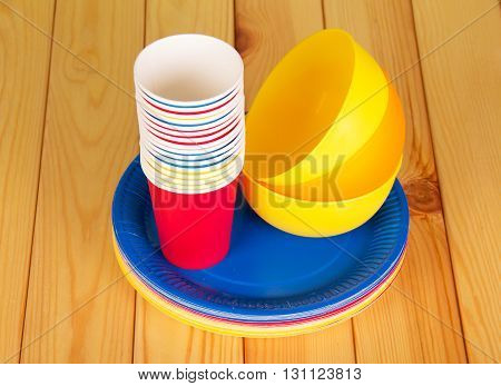 Bright plastic tableware on a background of light wood.
