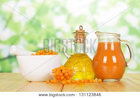 Bowls of sea buckthorn oil bottle and a jug of juice on abstract green background.
