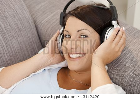 Happy young woman listening music on headphones, lying on sofa at home, smiling.?