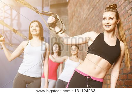 Pretty sporty girls are training with trx fitness straps. They are standing and stretching their body. The ladies are smiling