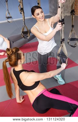 Beautiful young woman is fixing trx fitness straps before training. She is kneeling and smiling. Her trainer is helping her