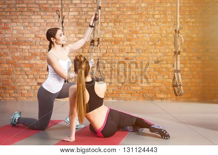 Attractive young girls are adjusting trx fitness straps. The woman is smiling. Her friend is sitting and helping