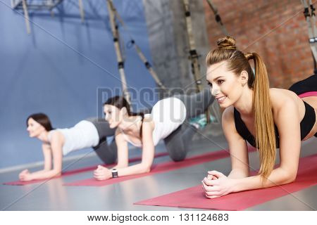 Pretty fit girls are doing plank exercise for back spine. Their legs are hanging on the trx straps. The ladies are laughing