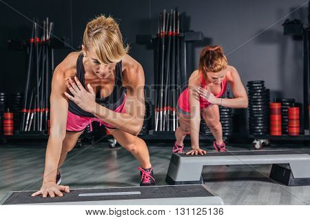 Closeup of women couple training hard over steppers in aerobic class on a fitness center. Sport and health concept.