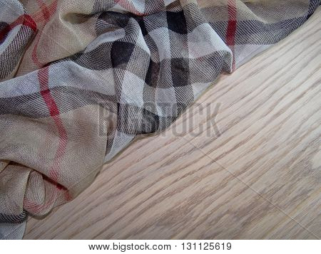 brown cloth with abstract drawings stacked pleats on wooden boards