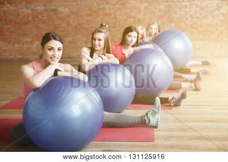 Beautiful young girls are resting after exercising. They are sitting on flooring and leaning arms on fitness ball. The ladies are looking at camera and smiling