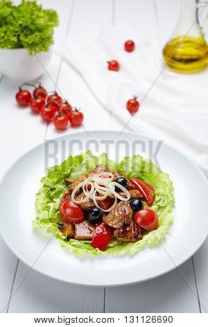 Grilled pork warm salad with sauce, tomatoes, champignon mushrooms, pepper and leek onion. Restaraunt menu meal in white dish on table background