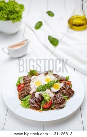 Veal beef fillet medallions warm salad with tomatoes, cucumber, cream sauce, basil and eggs. Restaraunt menu meal in white plate on table background.
