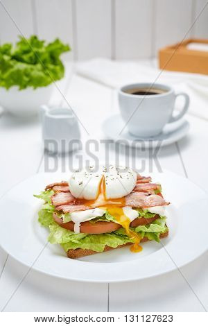 Poached egg sandwich with bacon, salad, mayonnaise, tomatoes, toasted bread and a cup of coffee. Concept of morning breakfast. Restaurant menu meal