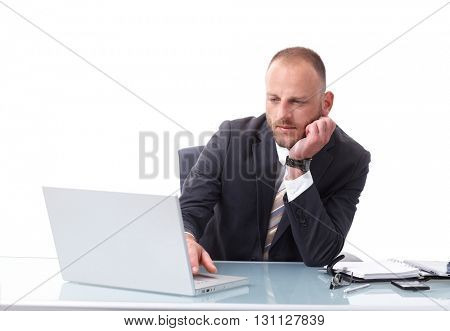 Businessman sitting at desk over white background, working with laptop computer, busy.