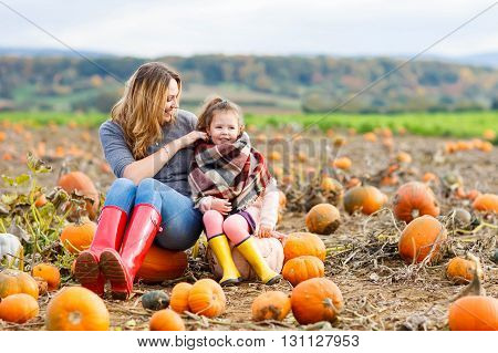 Beautiful young woman and little kid daughter, girl having fun with farming on a pumpkin patch. Traditional family festival with children, thanksgiving and halloween concept.
