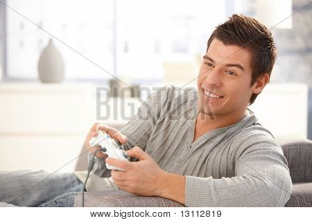 Young guy enjoying computer game, playing with joystick, smiling happily.?