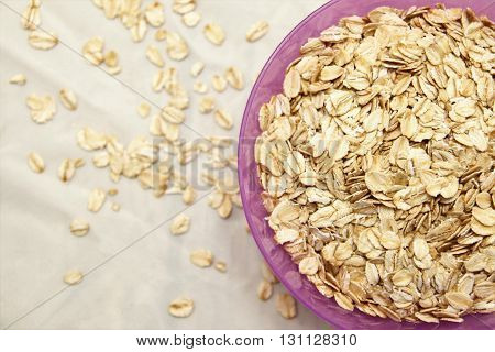 Rolled oats in the purple bowl on the white tablecloth, soft focus.