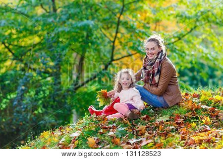 Young mother and her little daughter at beautiful autumn park. Kid girl and woman playing with yellow foliage. Family portrait outdoors.